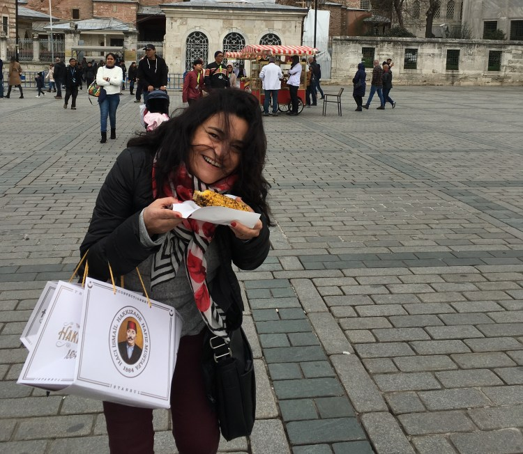 tour guide cristina duarte smiling and eating grilled corn on the cob