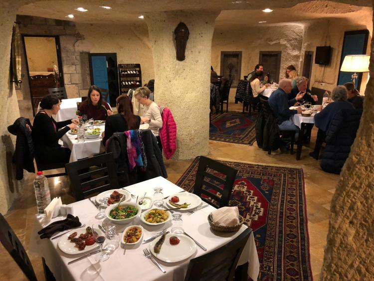 a restaurant with tables with produce and other food on them and tour guides sitting at the various tables having dinner and talking