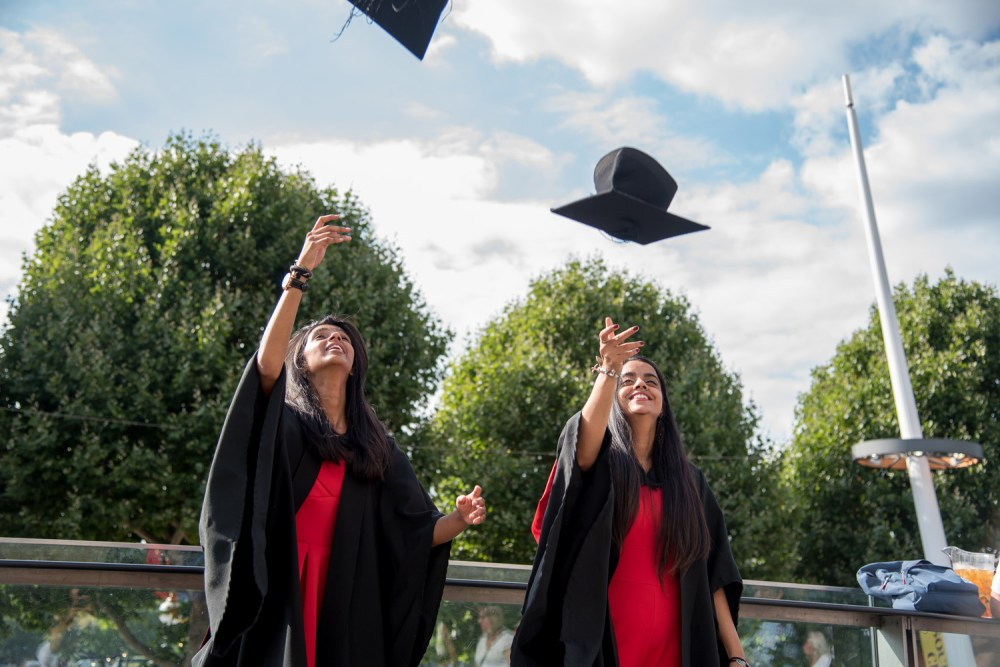 Two graduates engage in the ancient custom of Synchronised Hat Throwing, while wearing the traditional matching garb