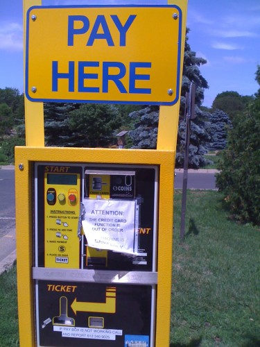 'PAY HERE' and taped-on sign in Arial