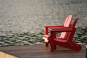 Two red deck chairs on a pier surrounded by water.
