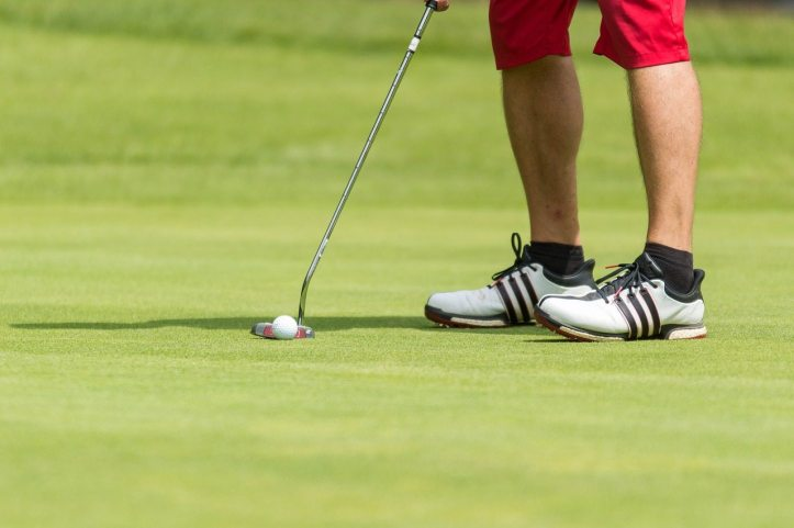 Close up shot of a person holding a golf club on a course.