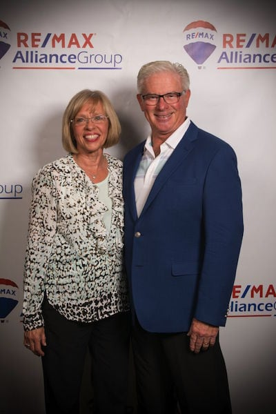 Real estate agents Terri and Dennis Kotaska standing in front of a backdrop with the words RE/MAX Alliance Group on the banner.