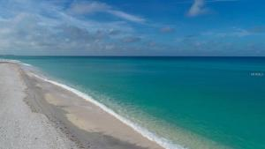 Beautiful shot of the ocean coast with turquoise blue water, bright sky, and white sand.