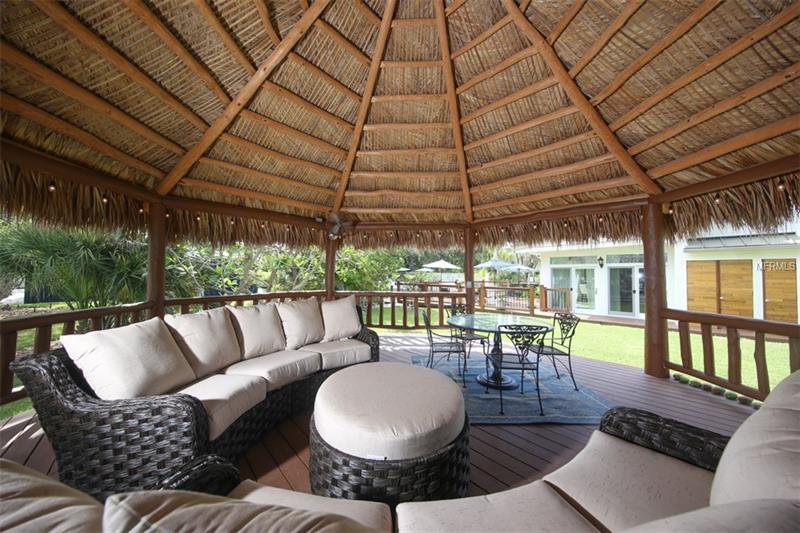 Huge outdoor tiki hut with spacious seating.