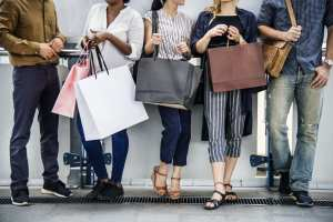 Group of adults holding shopping bags.