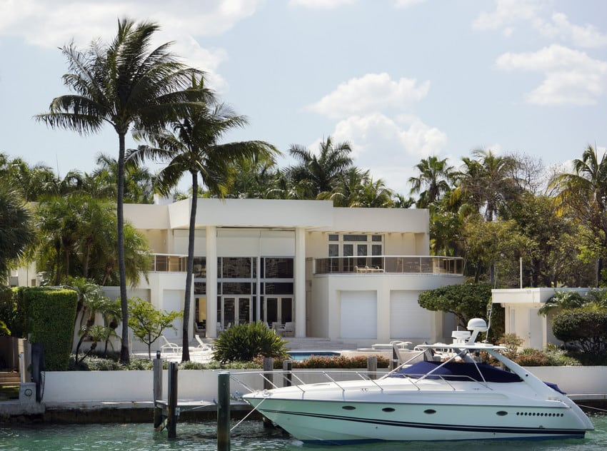 A Florida home on the water with a small yacht out front.
