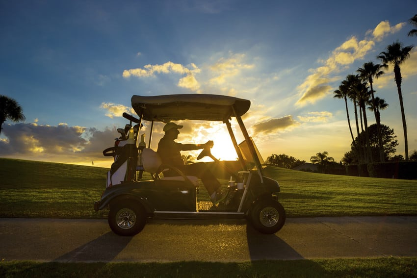 Man driving a golf cart at sunset.
