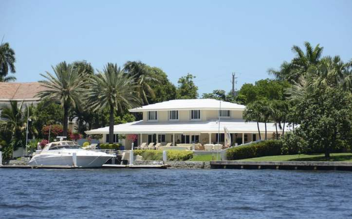 Luxurious Florida home with a white roof and yellow exterior that's right on the water.