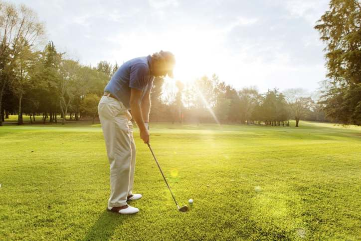 A man golfing on a lush golf course in the sun.