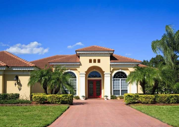 Classic Florida architectural style with an arch and palm trees out front.