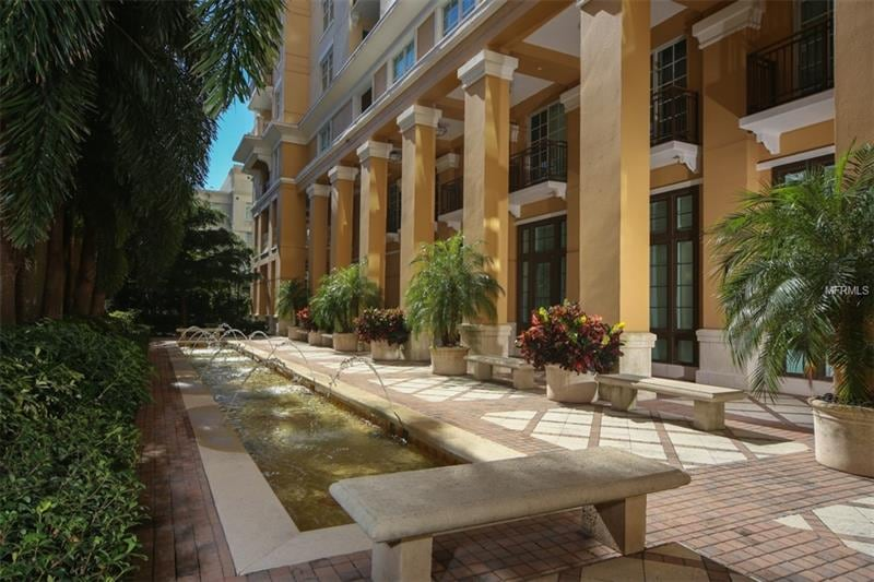 A beautiful promenade with light yellow columns and stone benches surrounding a pool.