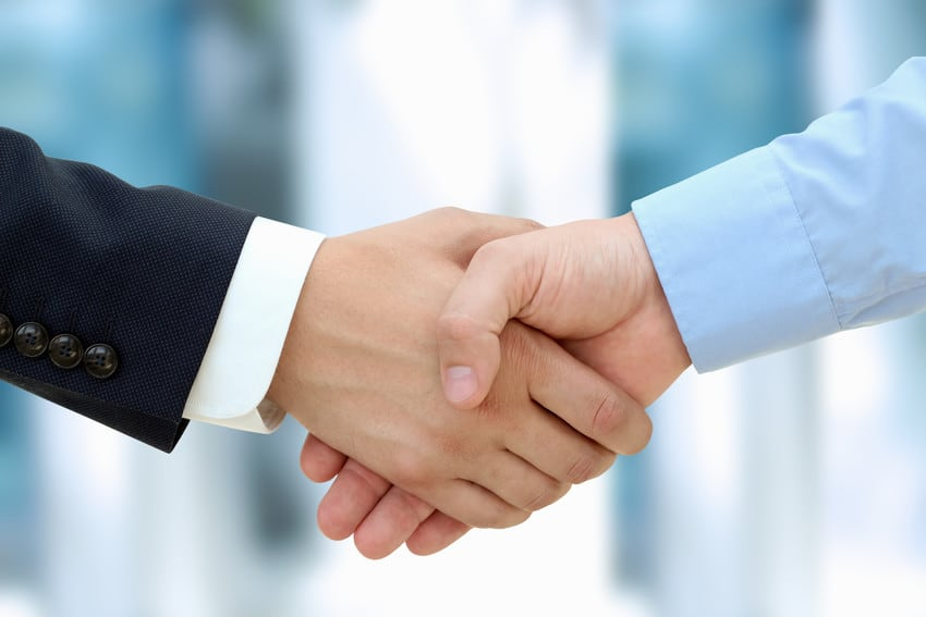 A close up photo of two men shaking hands.