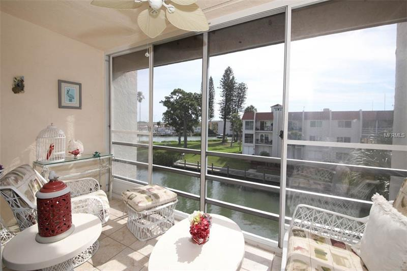 Screened-in patio with bright furniture and a water view.