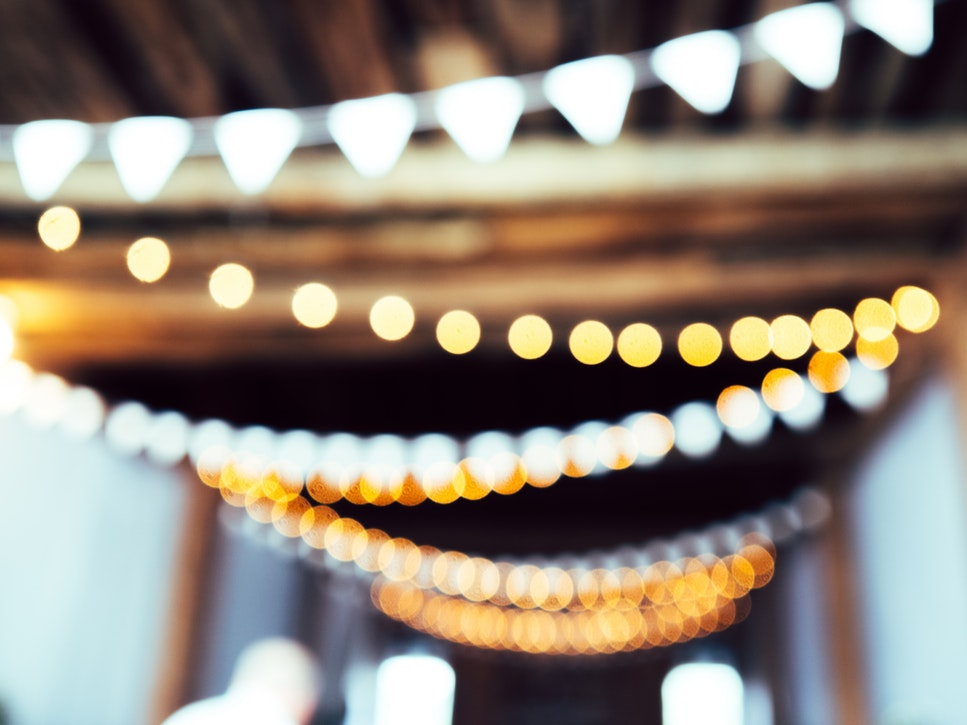 Blurry white lights hanging from a ceiling, how to decorate when selling during the holiday season.