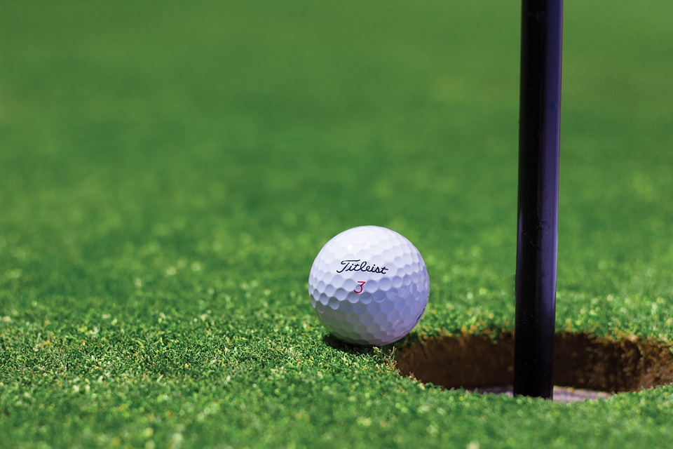 A golf ball about to enter a hole.