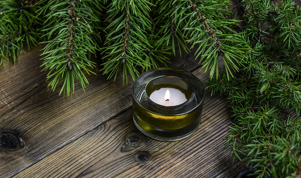 A candle sitting on a table surrounded by seasonal holiday greenery, how to stage when selling during the holiday season.