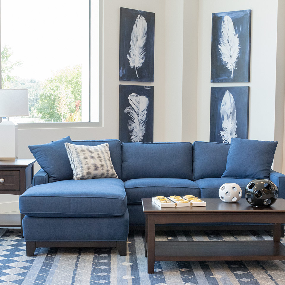 Living room with white walls, blue custom, reversible sectional, unique decorating accents