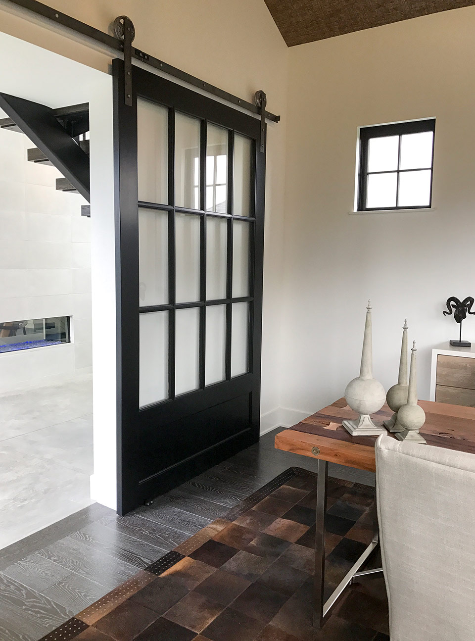 Home office with clean lines and unique decorating touches - gray wood floors, wide black barn door with window