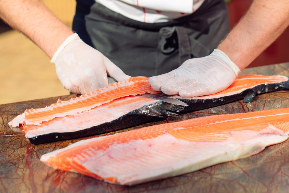 Cocinero retirando la espina de un salmón