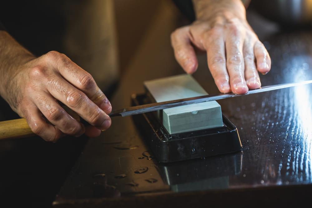 chef japonés afilando cuchillo