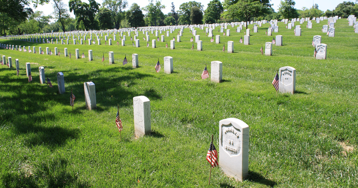 Who places the flags at Arlington National Cemetery gravesites for Memorial Day?
