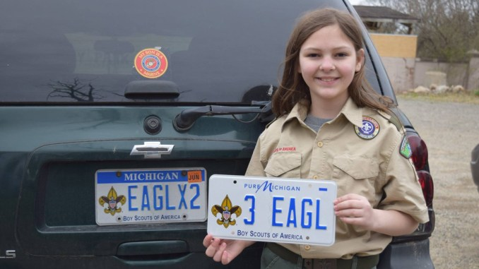 "Michaela holds a license plate saying ""3 Eagle"""