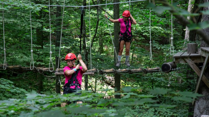 Venturers climb through the trees at the Summit Bechtel Reserve.