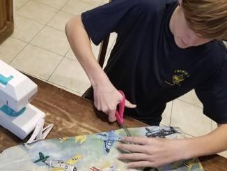 Rafe Kotalik of Troop 777 in the Woodlands, Texas (Sam Houston Area Council), makes face coverings to donate.