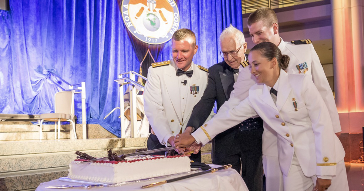 Harley Nygren helps cut the cake during the NOAA Corps Centennial Celebration in 2017.