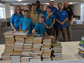 Austin (seated, middle) and his team pose for a photo after sorting books for his Eagle project, in a photo taken in September 2019.