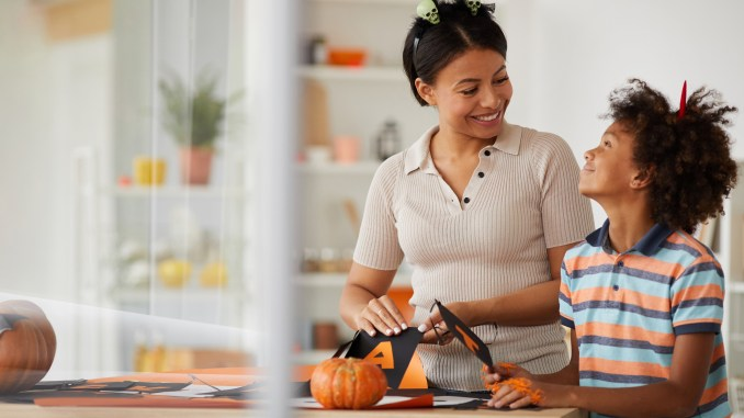 A mom and son decorate for Halloween