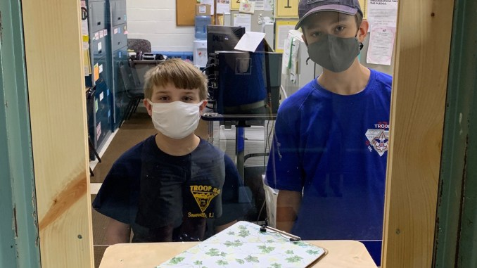 Lucas Davis (right) stands behind the plexiglass shield he constructed for his Eagle project. Among Lucas' project helpers: his cousin Nathan Davis (left), part of his pandemic cohort — individuals in his family who are only seeing each other.