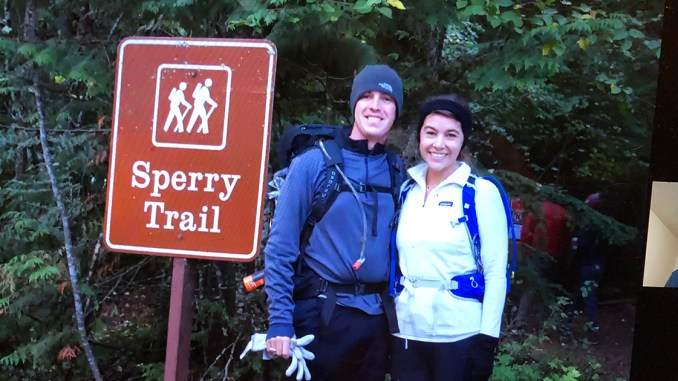 A couple smiles in front of a trailhead.