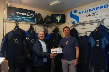 Ronan Murray accepting his prize from Breffni Gray, director of Scubadive West