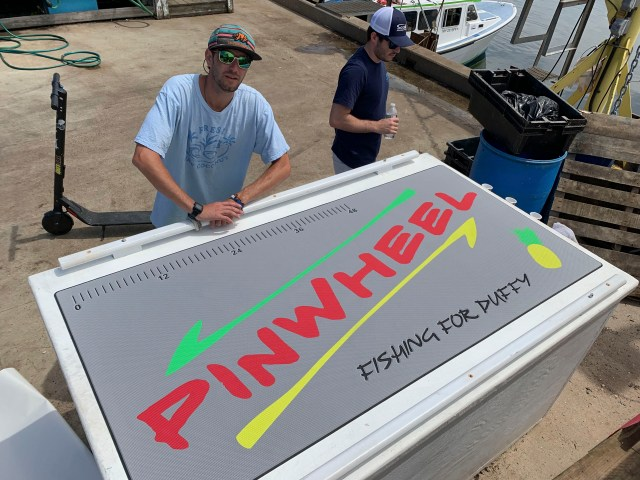 2 men standing next to a giant cooler with custom SeaDek on top that reads Pinwheel Fishing for Duffy that has also fish ruler and a pineapple.
