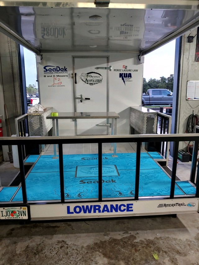 Custom SeaDek flooring in an enclosed trailer featuring the Osceola Anglers logo along with foot prints for the angler to stand on
