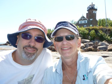 """David and Marge Back enjoy exploring Lake Superior. Their Sea Eagle 330 Sport Kayak is their """"full time transportation"""" while their sailboat is at anchor. Other times, it's their """"exploration kayak"""" as they kayak into sea caves. In the background is Lake Superior's Sand Island Lighthouse."""