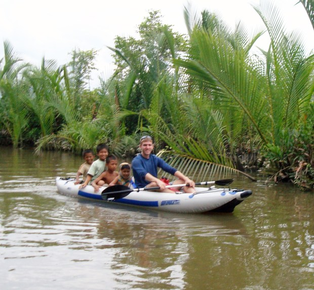 """Tim travels widely in Southeast Asia. Here, he's kayaking along the Kampot River in southern Cambodia.  """"I gave a few kids a ride along the way,"""" he says."""