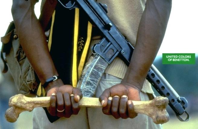 Zdjęcie człowieka z bronią trzmającego kość. © United Colors of Benetton / Oliviero Toscani