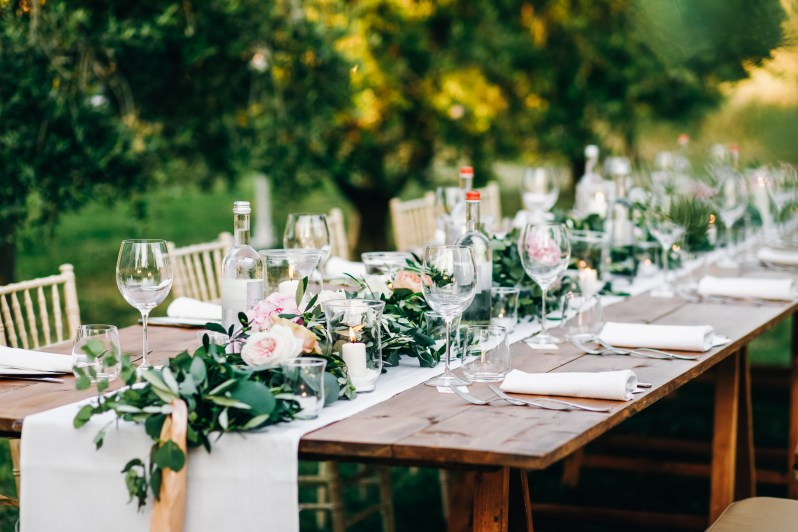 Floral garland of eucalyptus and pink flowers lies on the table