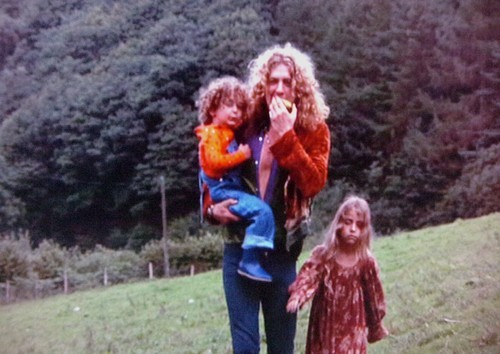 Robert Plant holding his son Karac and walking beside his daughter