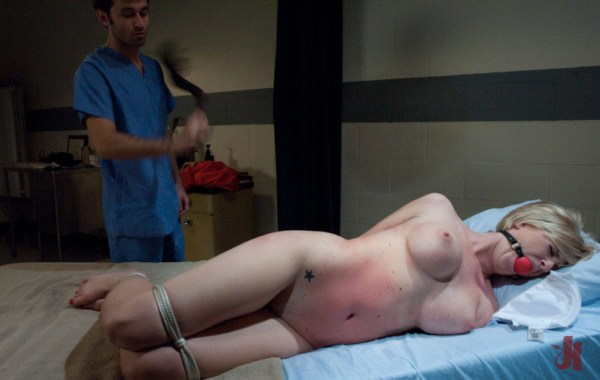 Cute blonde with a mouth gag gets flogged by her doctor in the examination room