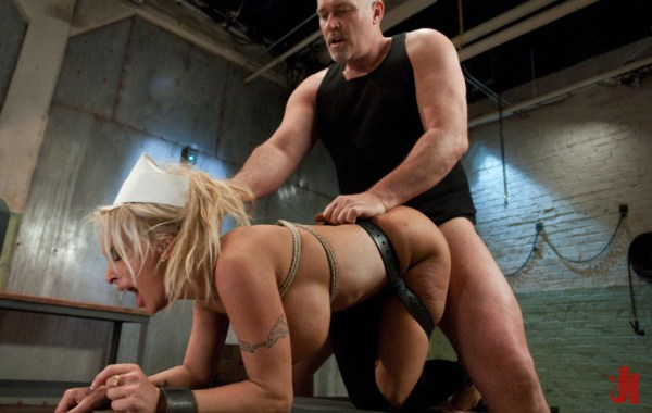 Naughty blonde is bound in leather and cuffed while fucked doggy-style by patient