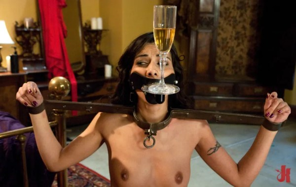 Skinny brunette is tied up in a medieval device and objectified to hold a glass of champagne