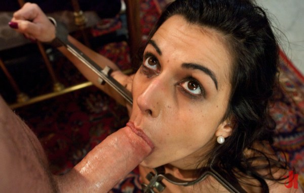 Petit brunette is forced to suck a big cock while having her hands bound in an iron device