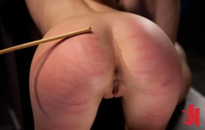 Submissive woman gets her ass caned hard while being put on her hands and knees