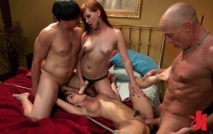 Dominant man fucks a brunette while another dominant man and woman fuck her throat