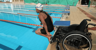 Nisha diving into the swimming pool from her wheelchair.