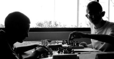 A black and white still from the film Algorithms, showing two people playing chess. There is a window behind them. The young man on the left is touching his chess pieces, while the one of the right is holding a chess piece from the top.